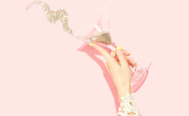 f3b722f342f5 Mão feminina, com unhas amarelas e traje rendado segurando uma taça de  martini com glitter