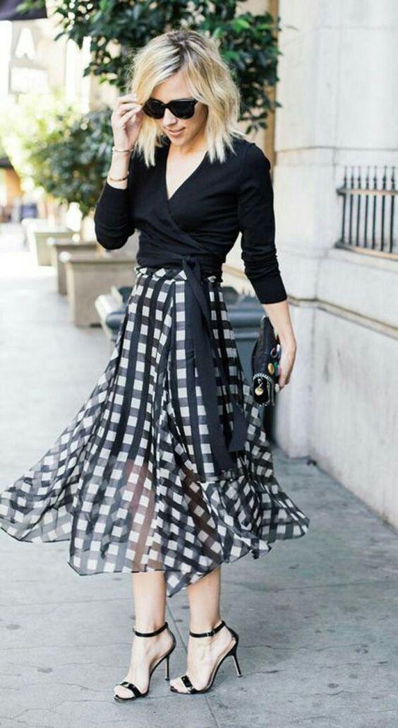 3c258d66e84a Moça de blusa preta amarrada na cintura e saia quadriculada com  transparência - traje que poderia